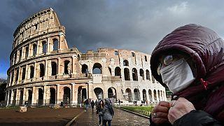 Un hombre con una máscara protectora pasa por el Coliseo de Roma el 7 de marzo de 2020 en medio del temor a la epidemia de Covid-19.