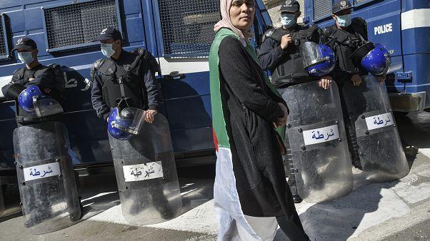 متظاهرة جزائرية تسير أمام أفراد الشرطة الذين وضعوا كمامات واقية خلال الحراك الأسبوعي بالعاصمة الجزائر. 06/03/2020