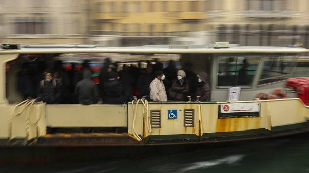 In this March 2, 2020 photo, commuters and locals take a bus boat in Venice, Italy.