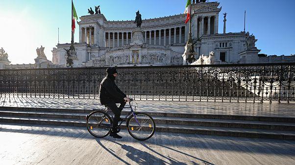 A man rides a bicycle past the Altare della Patria in Rome