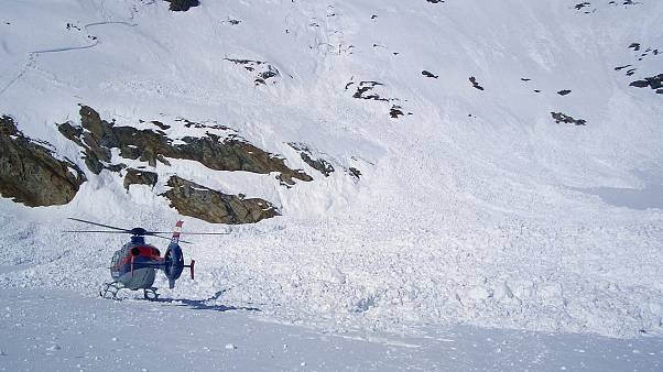 A helicopter is seen following an avalanche