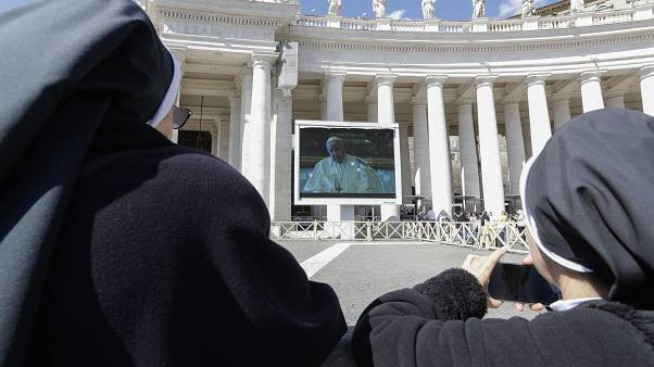 Nuns watch Pope Francis on a giant screen as he delivers the Angelus, in St. Peter's Square, at the Vatican, Sunday, March 8, 2020.