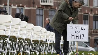 Rob Fredriksz, who lost his son Bryce and his girlfriend Daisy, places a sign next to 298 empty chairs, each chair for one of the 298 victims of the downed MH17.