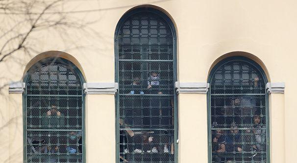 Presos tras las rejas de la prisión de San Vittore mientras estallaban las protestas por las restricciones impuestas a las visitas familiares para prevenir las transmisiones de coronavirus, en Milán, Italia, el lunes 9 de marzo de 2020.