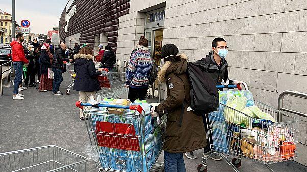 Des habitants de Milan, en Italie, portant des masques devant un supermarché, le 8 mars 2020.