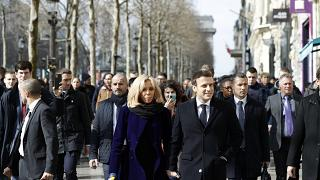 French President Emmanuel Macron and his wife Brigitte Macron walk down the Champs-Elysees avenue in Paris, Monday, March 9, 2020.