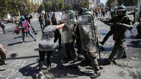 A woman struggles with riot police during clashes