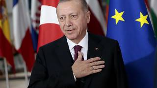 Turkish President Recep Tayyip Erdogan puts his hand over his heart in a gesture of hello prior to a meeting with European Council President Charles Michel.