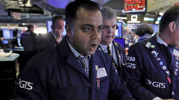 Specialist Dilip Patel, left, works at his post on the floor of the New York Stock Exchange, Monday, March 9, 2020
