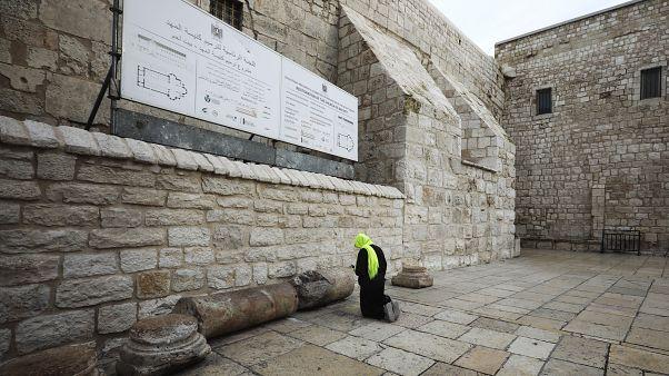 حاج مسيحي يصلي أمام كنيسة المهد في بيت لحم في الضفة الغربية المحتلة، حيث قررت السلطة الفلسطينية غلق الكنيسة بسبب انتشار فيروس كورونا