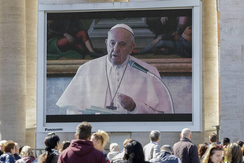 Los fieles ven al Papa Francisco pronunciar el rezo del Ángelus en una pantalla gigante para evitar que las multitudes se reúnan, en la Plaza de San Pedro, en el Vaticano, el domingo 8 de marzo de 2020.