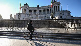 Un homme passe à vélo devant le monument Altare della Patria dans le centre de Rome, le 10 mars 2020.