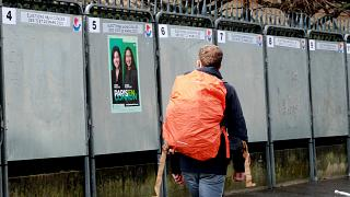 A man walks past a political poster depicting several of the candidats running in the upcoming French March 2020 mayoral elections.