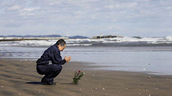 En hommage aux victimes du tsunami de 2011, un homme se recueille sur une plage d'Iwaki, dans le nord du Japon, le 11 mars 2020.
