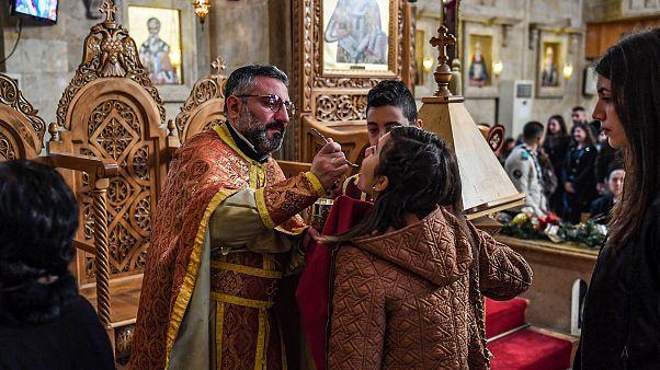 Fedeli ricevono la comunione con il rituale cucchiaino in una chiesa greca ortodossa siriana il 25 dicembre 2019 - AFP