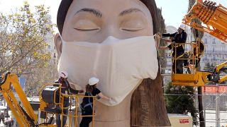 Munkások egy hatalmas maszkot helyeznek az egyik papírbábura a kelet-spanyolországi Valenciában