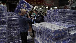A shopkeeper, left, is questioned by police officers as packs of bath tissue papers block a road in Hong Kong, Saturday, Feb. 8, 2020.
