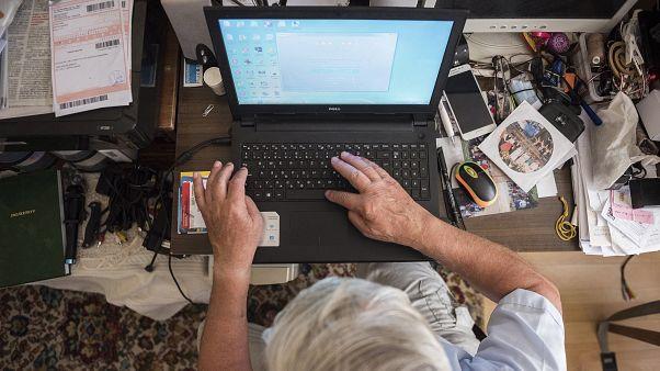 Otthonában laptopozik egy magyar férfi