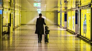 A woman walks with her suitcase down an empty corridor in the Rhine-Main Airport Thursday March 12, 2020.
