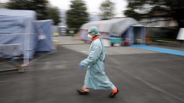 A staffer walks at one of the emergency structures that were set up to ease procedures at the Brescia hospital, northern Italy, Thursday, March 12, 2020.