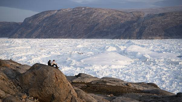 In this Aug. 16, 2019, file photo, NYU student researchers sit on top of a rock overlooking the Helheim glacier in Greenland.