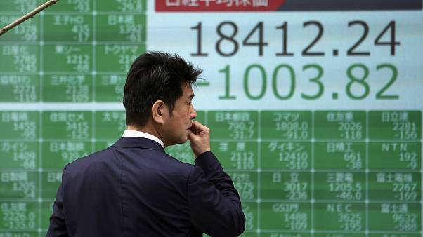 A man looks at an electronic stock board showing Japan's Nikkei 225 index at a securities firm in Tokyo Thursday, March 12, 2020.