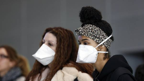 Women wear face masks at the Roissy Charles de Gaulle airport, north of Paris, Thursday, March 12, 2020.