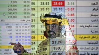 رجل أعمال سعودي يتحدث مع أخرين وخلفه شاشة كبيرة للسوق المالي في المصرف الوطني العربي بالعاصمة الرياض. 12/12/2019