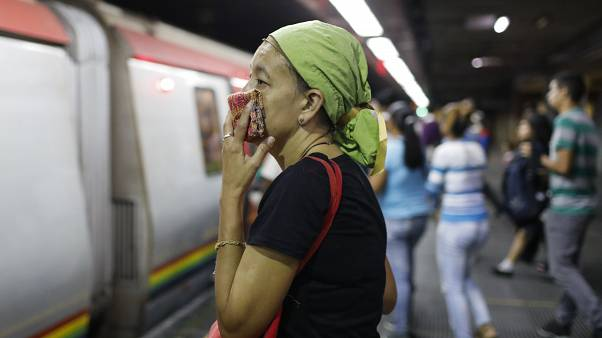 A woman covers her mouth and nose with a wash cloth on a subway platform in Caracas, Venezuela, Friday, March 13, 2020.