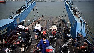 Passengers wearing face masks ride on a boat to cross the Yangtze river to Jiangzhou township in Jiujiang