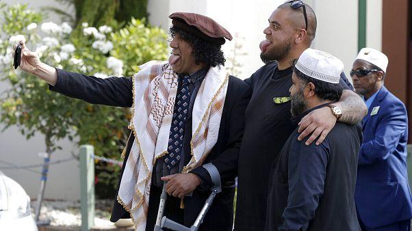 Al Noor mosque attack survivor, Taj Mohammad Kamran, left, takes a selfie with friends outside the Al Noor mosque in Christchurch, New Zealand