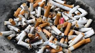 Cigarette butts are seen on a bin at a designated smoking area in Singapore on July 17, 2019. (Photo by ROSLAN RAHMAN / AFP)
