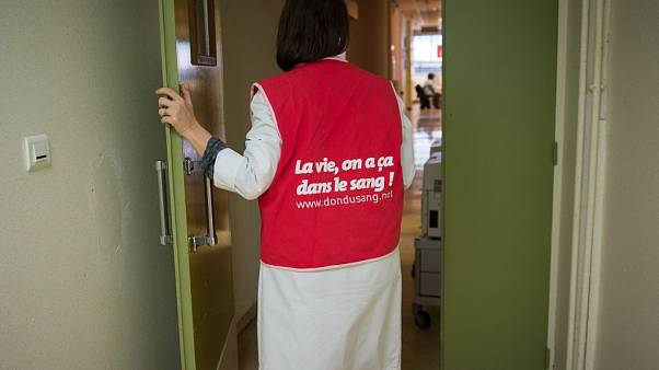 "A nurse wearing a jacket on which is written ""the life, it's in our blood"", Tours, central France. (Photo by GUILLAUME SOUVANT / AFP)"