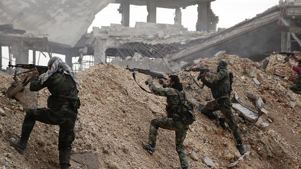 In this Dec. 5, 2016 file photo, Syrian army soldiers fire their weapons during a battle with rebel fighters at the Ramouseh front line, east of Aleppo, Syria.
