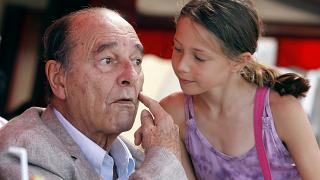 France's former president Jacques Chirac shows one of his cheek before a young girl gives him a kiss. FILE PHOTO August 2011