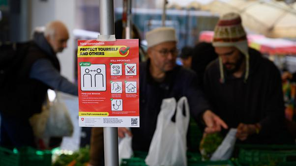 March 14, 2020 shows an information sign as eople are shopping in Saturday's market