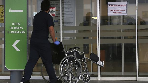 A hospital employment pushes a wheelchair into Nicosia General Hospital