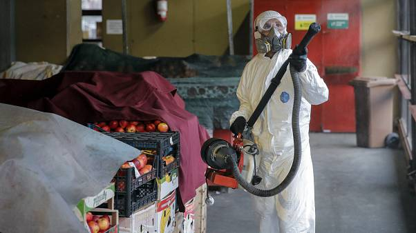 A man wearing protective gear sprays chemicals during the disinfection of a popular market, part of the efforts to limit the spread of Coronavirus, in Bucharest, March 2020