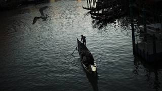 In this Feb. 28, 2020, file photo, a gondolier travels through the Grand Canal as the sun sets in Venice, Italy.