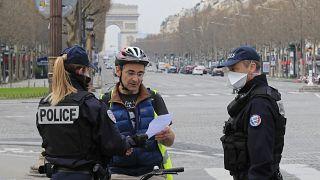 رجال شرطة يتحققون من وثيقة إذن بالخروج خاصة بمواطن بجادة الشانزليزيه