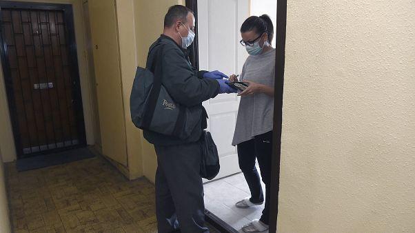Koronavírus - Védőfelszerelést viselő postás