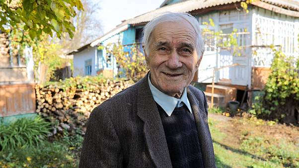 Ion Sandu, resident of old Cotul Mori, Moldova, stands in front of the house he refused to abandon