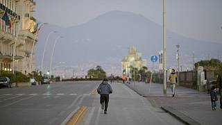 Un hombre haciendo deporte en las calles de Nápoles, frente al Vesubio, en plena cuarentena