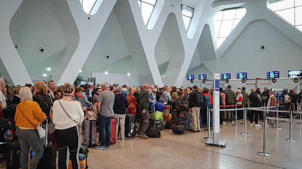 Passengers wait for their flights at the Marrakesh Airport on March 15, 2020