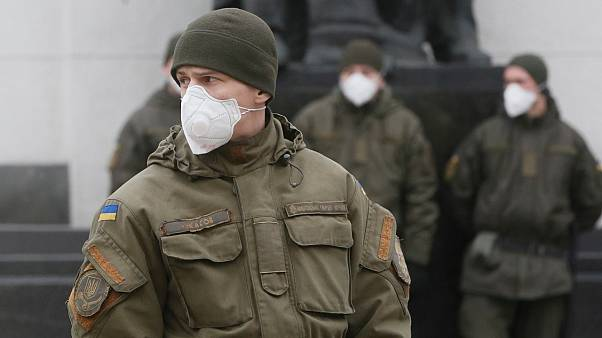 National guard soldiers wearing face masks stand at the parliament building in Kyiv, Ukraine, Tuesday, March 17, 2020.