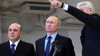 Moscow Mayor Sergei Sobyanin, right, points as he speaks to Russian President Vladimir Putin, center, and Prime Minister Mikhail Mishustin, left,.