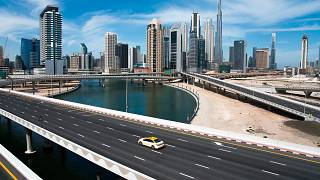 A lone taxi cab drives over a typically gridlocked highway with the Burj Khalifa, the world's tallest building, seen in the skyline behind it in Dubai, United Arab Emirates
