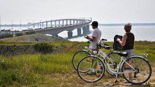 Des promeneurs à vélo admirent le pont de l'île de Ré, en Charente-Maritime - France - le 16 mai 2018