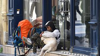 A homeless man hugs his dog as he sits along a deserted street on March 18, 2020