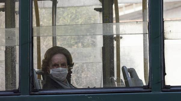 A woman wears a protective mask as she rides in a tram, in Rome, Wednesday, March 18, 2020.